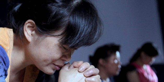 In this photo taken July 16, 2014, church members pray in a private room in Jiu'en Tang, a Christian church, in the Shuitou t