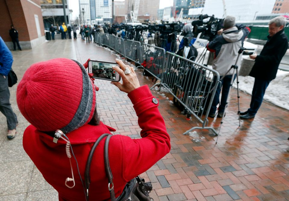 A woman photographs members of the media lined up outside federal court, Wednesday, March 4, 2015, in Boston, on the first da