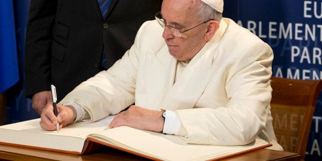 Pope Francis signs the guest book as President of the European Parliament Martin Schulz stands behind him, at the European Pa