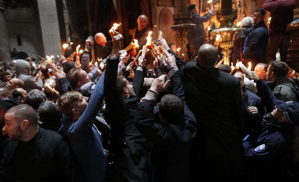 Christian Orthodox worshipers light candles from the 'Holy Fire' as thousands gather in the Church of the Holy Sepulchre.