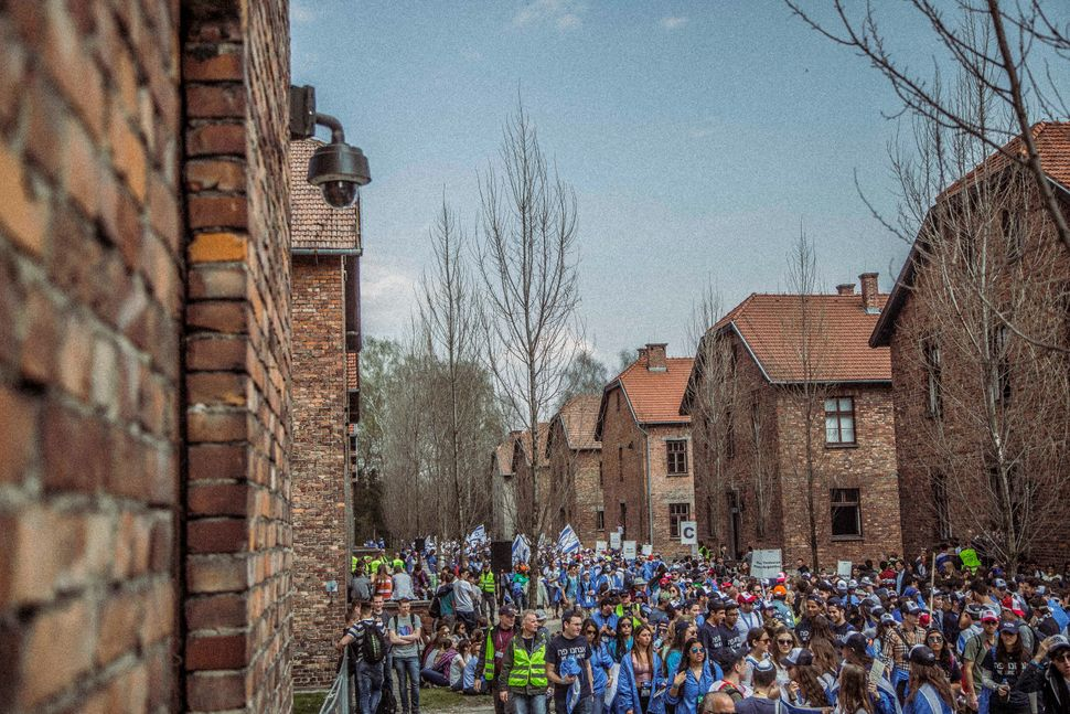 In Auschwitz, over 10,000 survivors and supporters fill the streets next to the barracks, preparing to march to Birkenau.