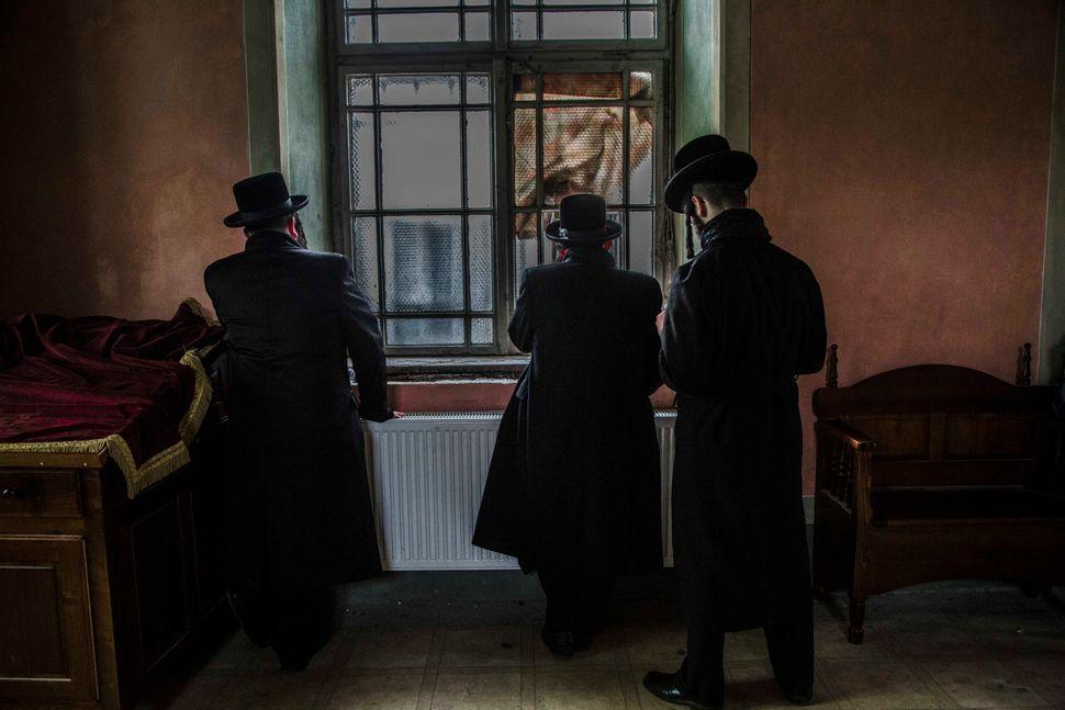 In the old Jewish quarter, three Hasidic Jews pray in an old temple.