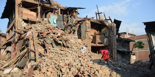 A woman walks amidst the rubble of collapsed houses in Bhaktapur, on the outskirts of Kathmandu, on April 27, 2015, two days