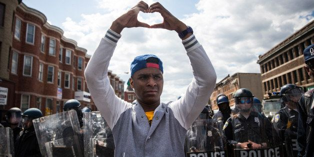 BALTIMORE, MD - APRIL 28:  A man makes a heart shape with his hands during a protest near the CVS pharmacy that was set on fi