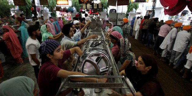 Volunteers wash used utensils inside the community kitchen at the Golden Temple, Sikh's holiest shrine, in Amritsar, India, F