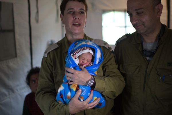 An Israeli army doctor holds the newborn baby of Nepalese woman, Quqila Pondari who was born during the night at the Israeli