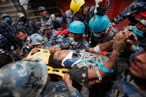 Pemba Tamang is carried on a stretcher after being rescued by Nepalese policemen and U.S. rescue workers from a building that