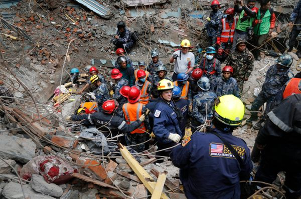 US rescuer workers, wearing yellow helmets, plan as they and Nepal policemen prepare to pull out Pemba Tamang, a teenage boy
