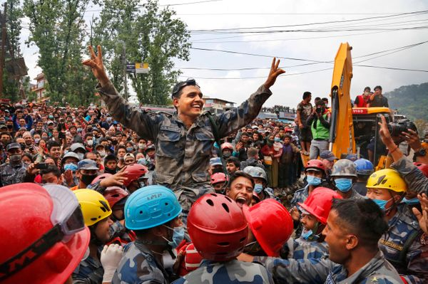 Nepalese policemen lift their commander and celebrate after they along with U.S. rescuers pulled out Pemba Tamang, a teenage
