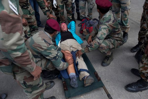 German trekker Simone Schiller grimaces as she lies on a stretcher after being rescued from Lukla by an Indian Air Force heli