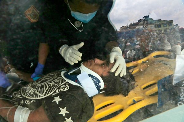 A U.S. doctor attends to Pemba Tamang inside an ambulance after being rescued by Nepalese policemen and U.S. rescue workers f