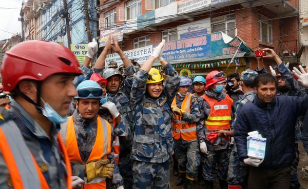 Nepalese policemen cheer after they  along with U.S. rescuers pulled out Pemba Tamang, a teenage boy from a building that col