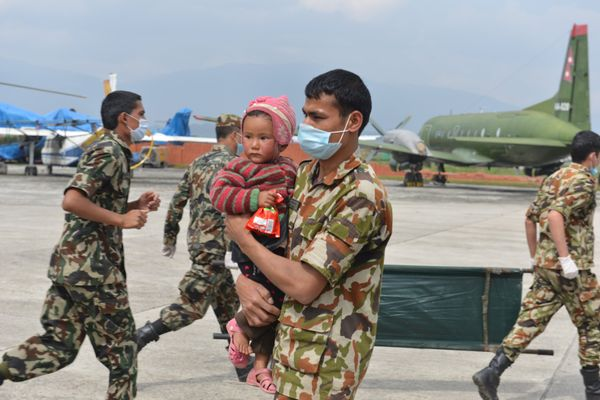 Nepalese Army personnel carry a rescued child at the airport in Kathmandu on April 30, 2015. The UN launched an appeal for Ne