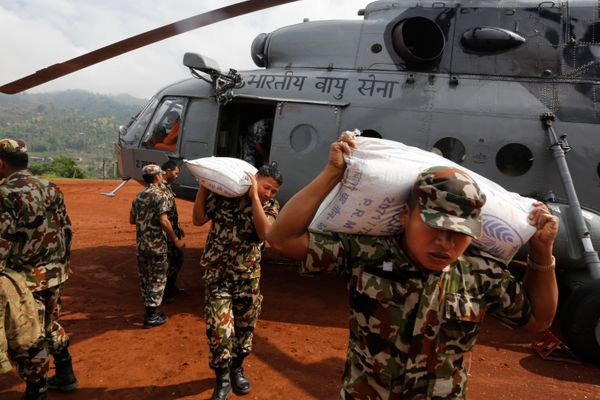 Nepal army soldiers unload relief material from an Indian Air Force helicopter at earthquake affected Dhadingbesti, in Nepal,