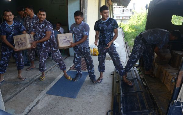 Nepalese police force personnel unload relief aid at a warehouse, prior to distribution to earthquake-affected villages, in B