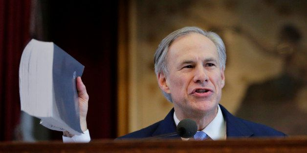Texas Gov. Greg Abbott holds a book about Texas school laws as he delivers his State of the State address to a joint session