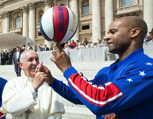 Harlem Globetrotters' Flight Time Lang, right, helps Pope Francis spin the ball on his finger as they meet during the general