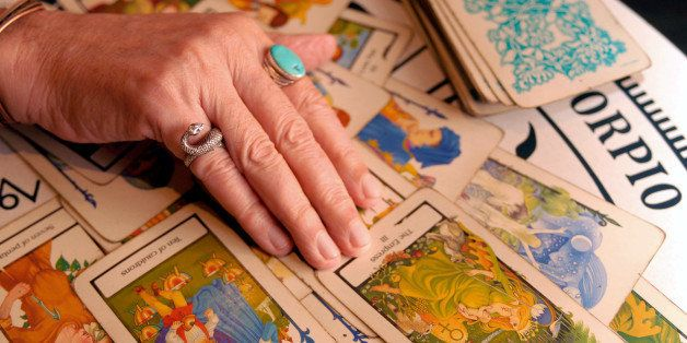 ** ADVANCE FOR SUNDAY, AUG. 26 ** Psychic and Tarot card reader Otis Biggs reads a spread of Tarot cards as a positive sign f