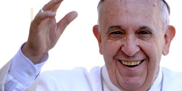 Pope Francis salutes the crowd as he arrives for his weekly general audience in St Peter's square at the Vatican on April 22,