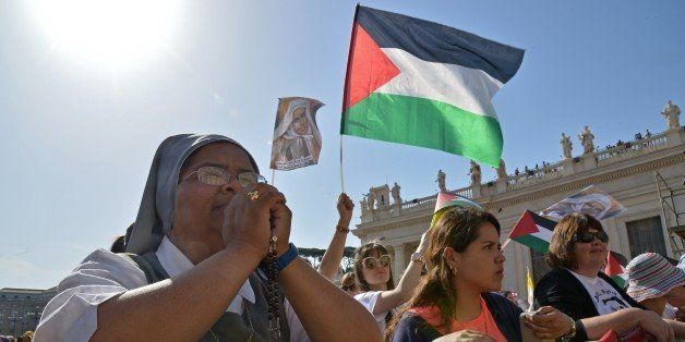 Pilgrims wave Palestinian flags before a holy mass in St Peter's square for the canonization of four blessed nuns, whose two