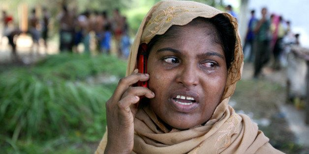 An ethnic Rohingya woman cries as she uses her phone to call a relative back home, at a temporary shelter in Langsa, Aceh pro