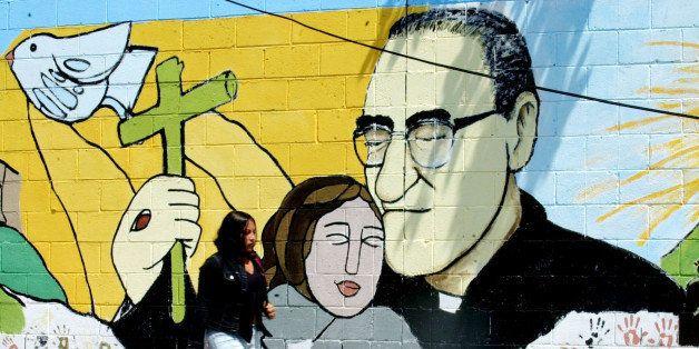 A woman passes a mural of slain Bishop Oscar Arnulfo Romero in Santa Tecla, some 8 miles from San Salvador, Tuesday, March 22