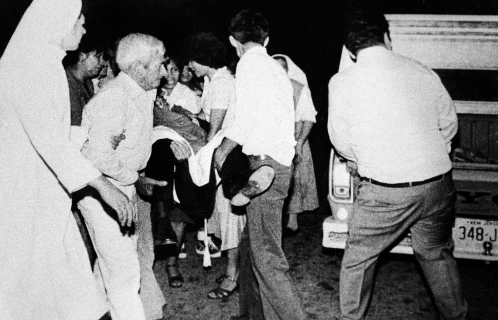 Monsignor Oscar Arnulfo Romero is carried to a waiting improvised ambulance for a futile trip to a nearby hospital, March 25,
