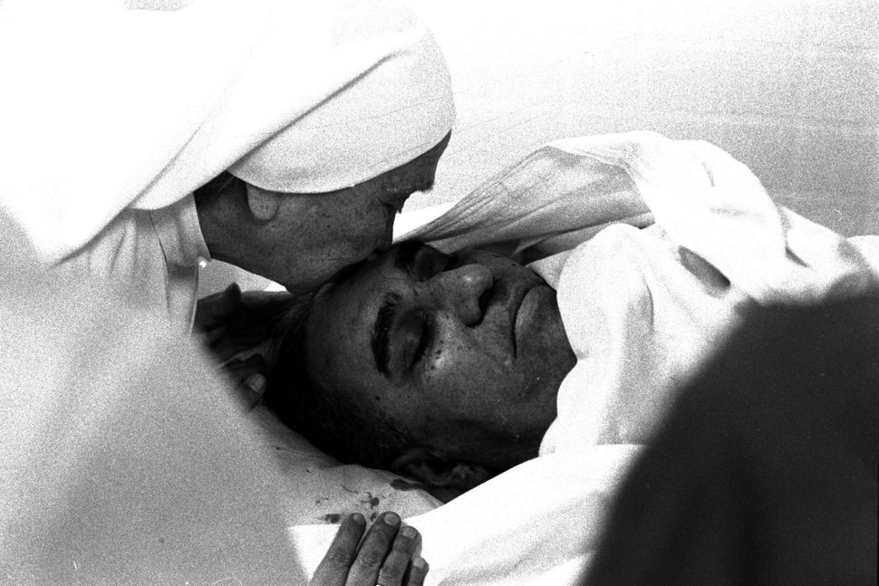 A nun plants a kiss on the forehead of assassinated Archbishop Oscar Arnulfo Romero at the Hospital of Divine Providence in S