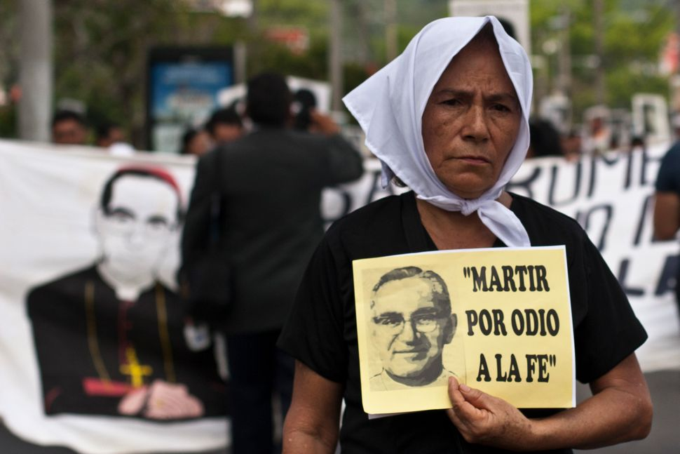 "A woman carries a portrait of slain Roman Catholic Archbishop Oscar Romero that reads in Spanish: ""Martyred by faith haters,"""