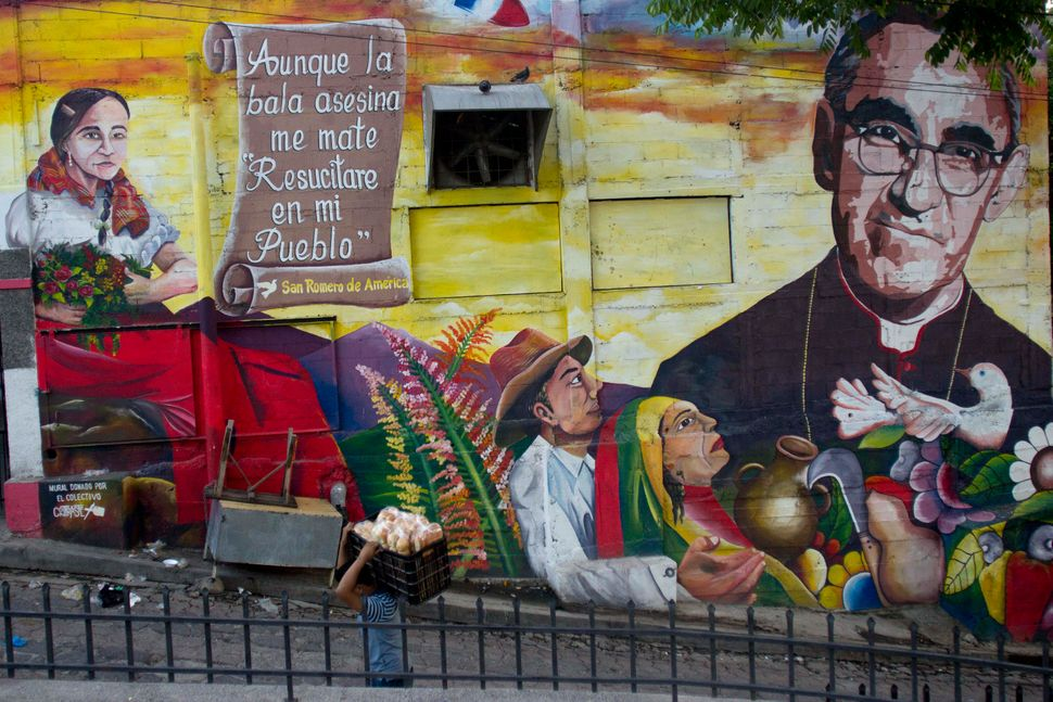 A mural of Roman Catholic Archbishop Oscar Romero decorates a wall in a street where a man carries bread in Panchimalco, El S
