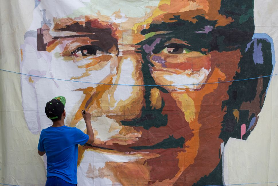 In this March 15, 2015 photo, a young man paints a portrait of Archbishop Oscar Arnulfo Romero as part of the preparations fo