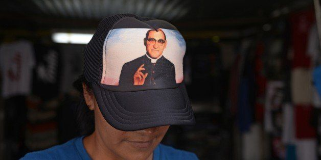 A vendor wears a cap with the portrait of Salvadorean Monsignor Oscar Romero (1917-1980) in San Salvador on May 19, 2015. Mon