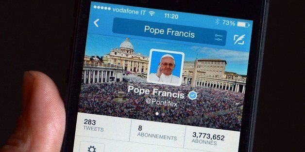 A mobile phone displays a tweet of Pope Francis reading 'Please pray for me' on his @Pontifex twitter account on March 13, 20