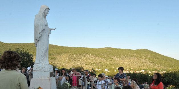 Catholic pilgrims gather kneeling around a statue of Virgin Mary, overseeing the area around a pilgrimage site near the South