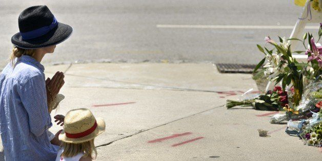 A woman prays at a makeshift memorial near the Emanuel AME Church June 18, 2015 in Charleston, South Carolina, after a mass s