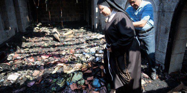 A nun inspects the damage at a room located on the complex of the Church of the Multiplication at Tabgha, on the shores on th
