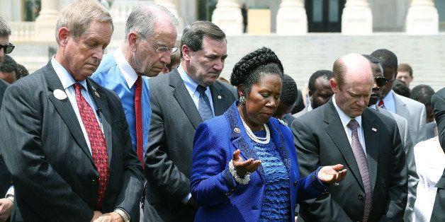 WASHINGTON, DC - JUNE 18:  Rep. Sheila Jackson Lee (D-TX) (C) prays alongside Rep. Joe Wilson (R-SC) (L), Sen. Chuck Grassley