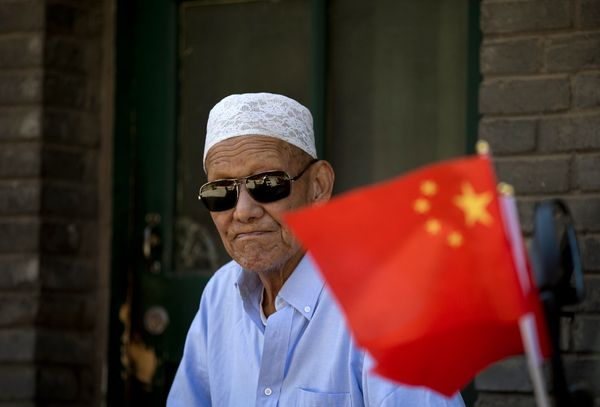 A Chinese Hui Muslim man sits near the national flags stick on a motorbike parked at the Nuijie Mosque on the first day of th