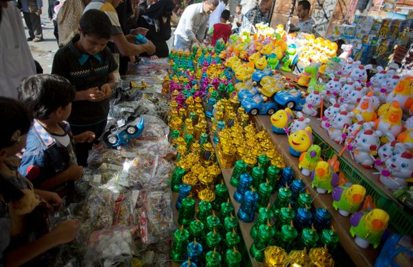 In this Wednesday, June 17, 2015 photo, Palestinian children buy traditional Ramadan lanterns to celebrate the announcing of