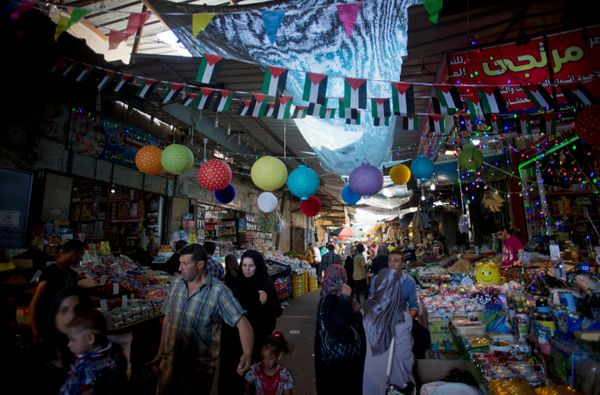 In this Wednesday, June 17, 2015 photo, Palestinian vendors decorate the market with lanterns and national flags celebrating