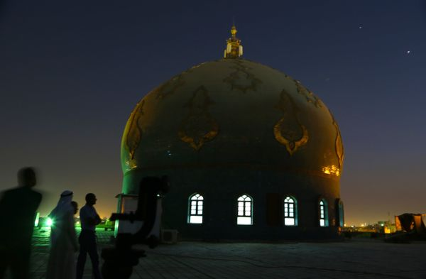 Iraqi Muslim men gather, on the roof of Imam Ali  Mosque, waiting to see the crescent moon marking the beginning of Ramadan,