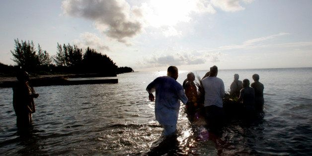 A group of men wade into the ocean as they push a small raft loaded with offerings to their ancestors out to sea Sunday, June