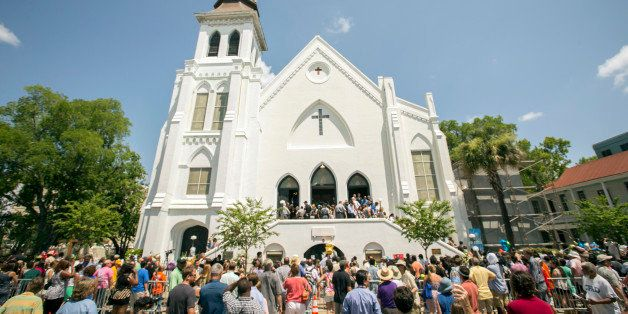 People stand outside as parishioners leave the Emanuel A.M.E. Church, Sunday, June 21, 2015, in Charleston, S.C., four days a