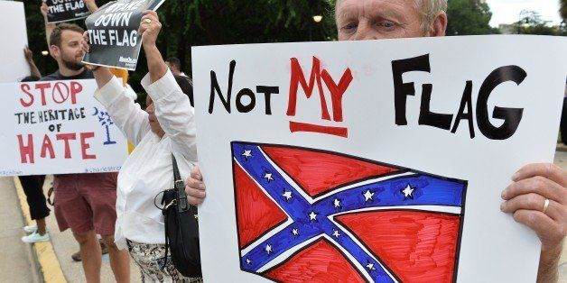 A man holds a sign up during a protest rally against the Confederate flag in Columbia, South Carolina on June 20, 2015. The r