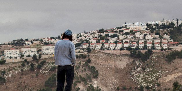 FILE - In this Wednesday, Dec. 5, 2012 file photo, a Jewish settler looks at the West bank settlement of Maaleh Adumim, from
