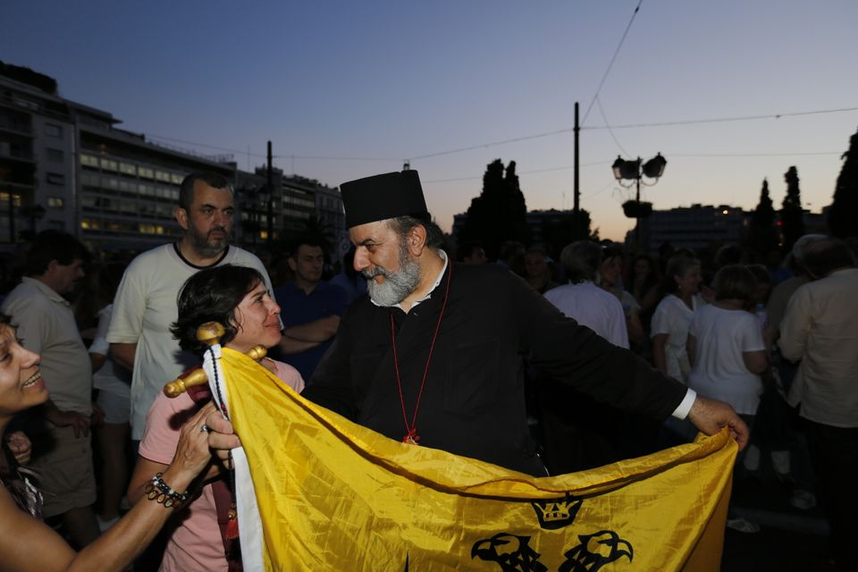 SYNTAGMA SQUARE, ATHENS, ATTICA, GREECE - 2015/06/17: An orthodox priest, carrying a flag of the Greek Orthodox Church, takes