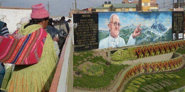An indigenous woman is seen near a mural of Pope Francis in El Alto, Bolivia on July 3, 2015. Pope Francis will make a three-