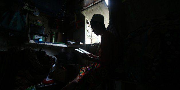 In this July 9, 2015, photo, Filipino Muslim Munib Dalidig reads the Koran inside his home in suburban Tumana, Marikina city,