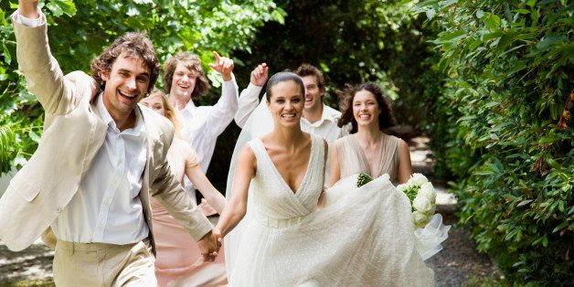 Wedding party running in garden