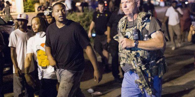 FERGUSON, MO - AUGUST 10:  Oath Keepers, carrying rifles, walk along West Florrisant Street as  demonstrators, marking the fi